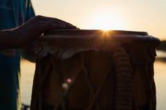 Jogando um jembe ou um atabaque do instrumento musical no céu do fundo no por do sol imagem de stock