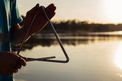 Jogando um triângulo do instrumento musical no céu do fundo no por do sol foto de stock