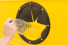 Jogando uma garrafa no recipiente de reciclagem Imagens de Stock Royalty Free