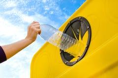 Jogando uma garrafa no recipiente de reciclagem Imagens de Stock