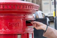 Jogando uma letra em uma caixa britânica vermelha do cargo Foto de Stock