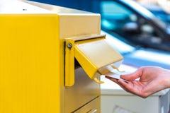 Jogando uma letra em uma caixa postal amarela Foto de Stock