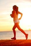 Jogga idrottsman nenkvinnaspring på solsolnedgången sätta på land Royaltyfri Bild