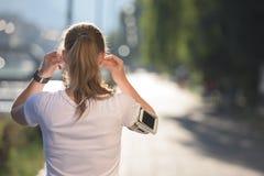 Jogga kvinnainställningstelefonen, innan att jogga royaltyfria bilder