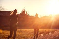 Jogga kvinnan och den sportiga mannen som kör över glödande solsken, Spor fotografering för bildbyråer