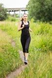 Jogga kvinnan på sommarmiddagar Royaltyfria Bilder