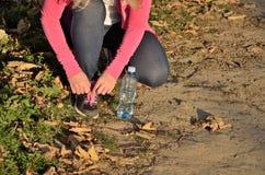 Jogga kvinnan som binder skosnöre på hennes gymnastiksko Royaltyfria Foton