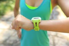 jogger έτοιμος να τρέξει το σύνολο και την εξέταση το αθλητικό έξυπνο ρολόι Στοκ Φωτογραφίες