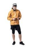 Jogger в куртке кладя jack наушников в smartphone Стоковые Изображения