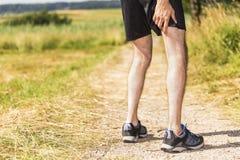 Jogger имея боли в мышцах Стоковые Изображения RF