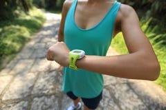 Jogger молодой женщины готовый для того чтобы побежать установленное и смотреть вахта спорт умный Стоковые Изображения