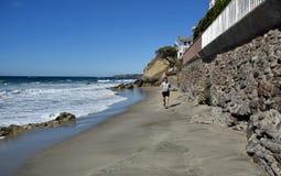 Jogger на пляже улицы жемчуга вдоль береговой линии южной Калифорнии в южном пляже Laguna Стоковые Изображения RF