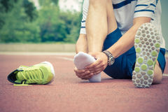 Jogger checking if his ankle is broken or twisted. Jogger hands on foot. He is feeling pain as his ankle or foot is broken or twisted. Accident on running track Stock Photos