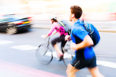 Jogger and cyclist in city traffic Royalty Free Stock Photo