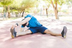 Jogger Doing Workout Before Running On Track In Park. Flexible jogger doing workout before running while sitting on track in park stock photos
