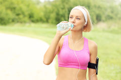 Jogger drinking water in the park Stock Image