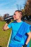 Jogger drinking water after workout. Young man drinking water after workout royalty free stock image