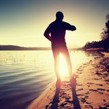 Jogger in fitness clothing running along beach coast with the blue skyand sunrise Stock Photos