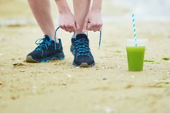 Jogger with green vegetable smoothie, tying sport running shoes laces Stock Photo