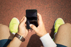 Jogger holding smartphone with blank screen Royalty Free Stock Photo