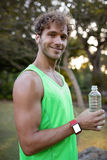 Jogger holding water bottle in park Royalty Free Stock Photo