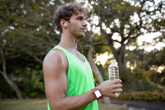 Jogger holding water bottle in park Stock Photography