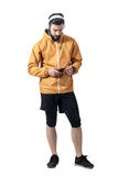 Jogger in jacket putting headphones jack in smartphone Stock Images