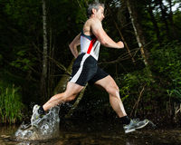 Jogger in a jump through a streambed Royalty Free Stock Image