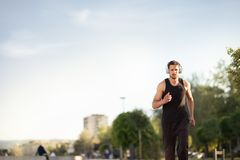 Jogger listening to training music on headphones. Running man - male runner listening to music on headphones, sporty fit young man jogging royalty free stock photos
