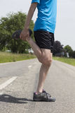 Jogger man stretching his legs Stock Photos