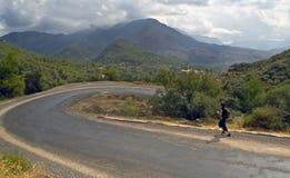 Jogger op kronkelige weg in bergen Stock Foto's