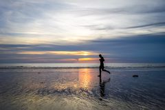 Jogger på Nai Yang Beach på solnedgången, Phuket, Thailand royaltyfri fotografi
