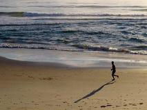 Jogger på stranden på soluppgång Arkivbilder