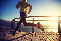 Jogger ranku ćwiczenie na nadmorski boardwalk podczas wschodu słońca zdjęcia stock