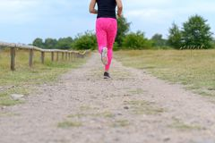Jogger running away from camera at low angle. Female adult jogger wearing sweatpants running away from camera at low angle along grassy road next to fence royalty free stock photos