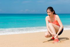Jogger running on beach feeling ankle painful. Beautiful jogger running on beach feeling ankle painful uncomfortable Stock Photography