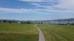 Jogger running on a country road in beautifull environment on a long road. Endurance. In Zug Switzerland