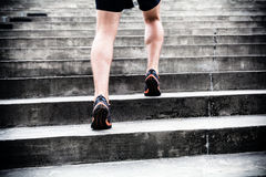 Jogger running on stairs, sports training. Man runner running on stairs in city, sport training. Young male jogger athlete training and doing workout outdoors in Stock Photo