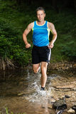 Jogger running through a streambed Stock Photo