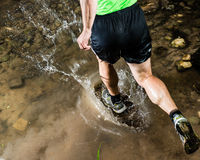 A jogger is running through a streambed Royalty Free Stock Images