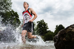 Jogger running through a streambed Royalty Free Stock Photos