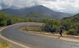 Jogger on serpentine road in mountains. Young man wearing shorts and backpack runs down the serpentine road in mountains in cloudy weather Stock Photos