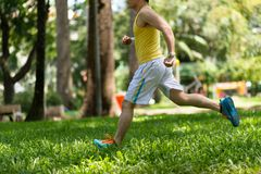 Jogger. Side view of jogger running on the grass Stock Photos