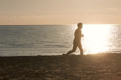 Jogger silhouette on beach Stock Image