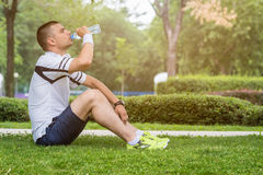 Jogger sitting on the grass and drinking water Royalty Free Stock Images
