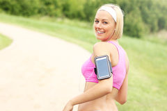 Jogger with smartphone in the park Royalty Free Stock Photography