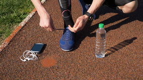 Jogger with smartwatch tying shoelaces and picking smartphone with earphones and water bottle. Jogger with smartwatch tying shoelaces and picking up smartphone stock video footage