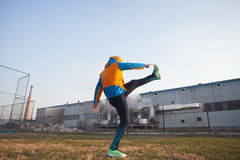 Jogger standing on one leg and stretching Royalty Free Stock Images