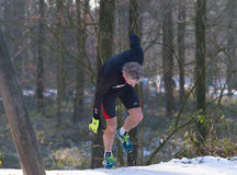 Jogger stumbles in snow. OLDENZAAL, NETHERLANDS - JANUARY 22, 2017: Unknown athlete stumbles up a hill during a cross run in a snow white landscape Stock Photo