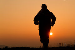 A jogger in sunset. A jogger is running in sunset Royalty Free Stock Image